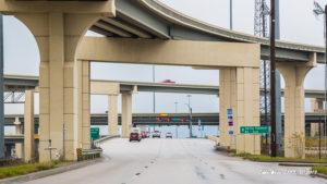 Two memorial crosses against the pillar of a highway bridge.