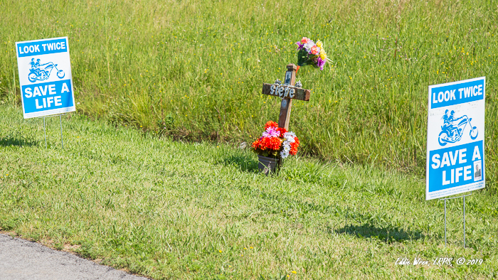 Roadside memorial, accompanied by a safe motorcycling message.