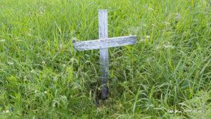Dilapidated roadside memorial cross in long grass.