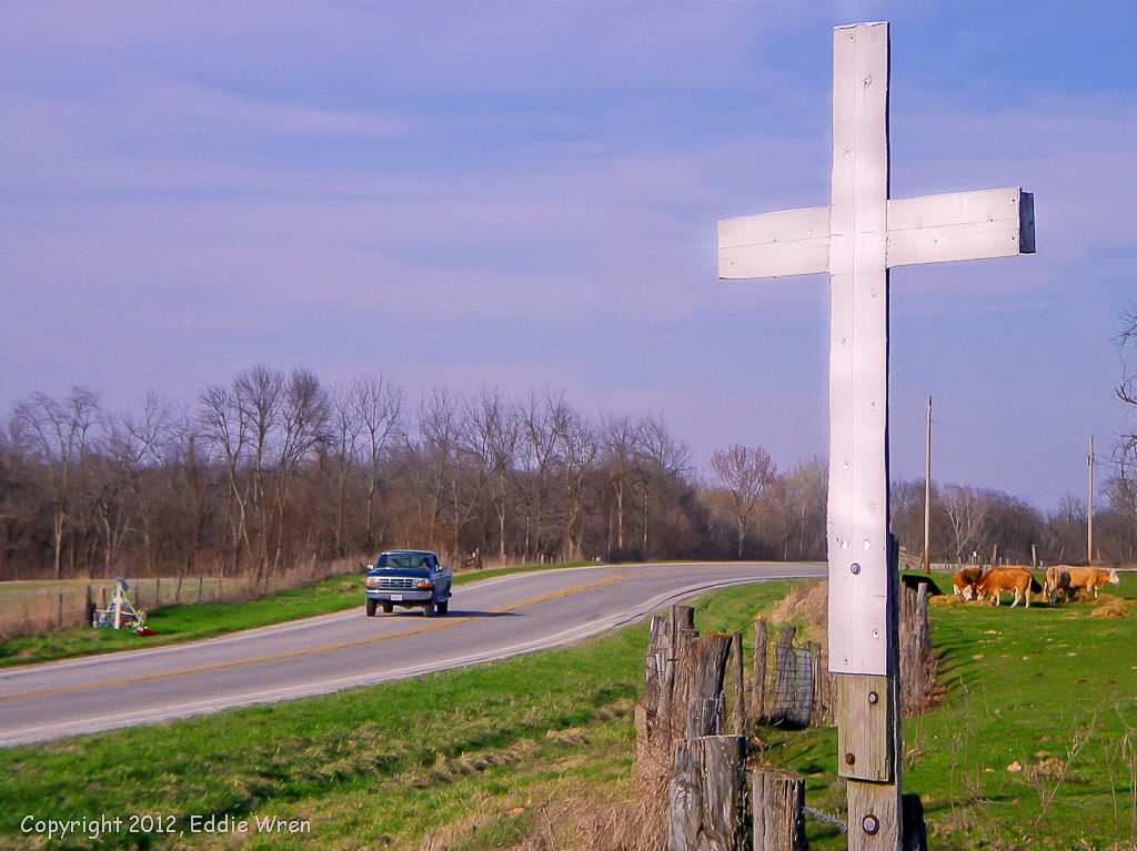 Two roadside memorial crosses on one curve.
