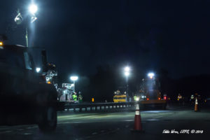 A nighttime photograph of a construction zone on an interstate highway showing several workers on foot.