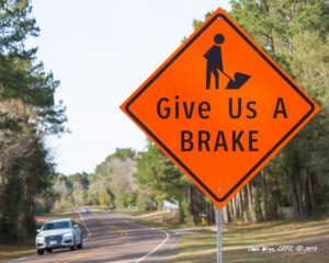 An orange construction zone sign with a deliberate spelling mistake for double-meaning: Give Us a Brake.