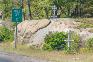 Two roadside memorials to people killed in seaparate crashes at the same location.