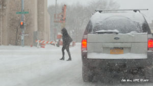 Pedestrian and SUV in snowy conditions.