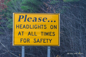 A road sign / traffic sign in Massachusetts, advising drivers to keep headlights on at all times.