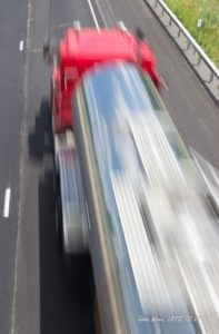 A view down onto a fast-moving semi-tractor-trailer.
